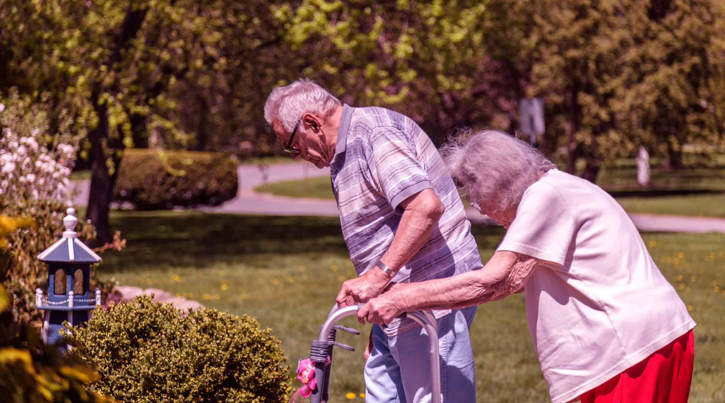 Um idoso e uma idosa caminham em uma paisagem verde | perda de coordenação motora