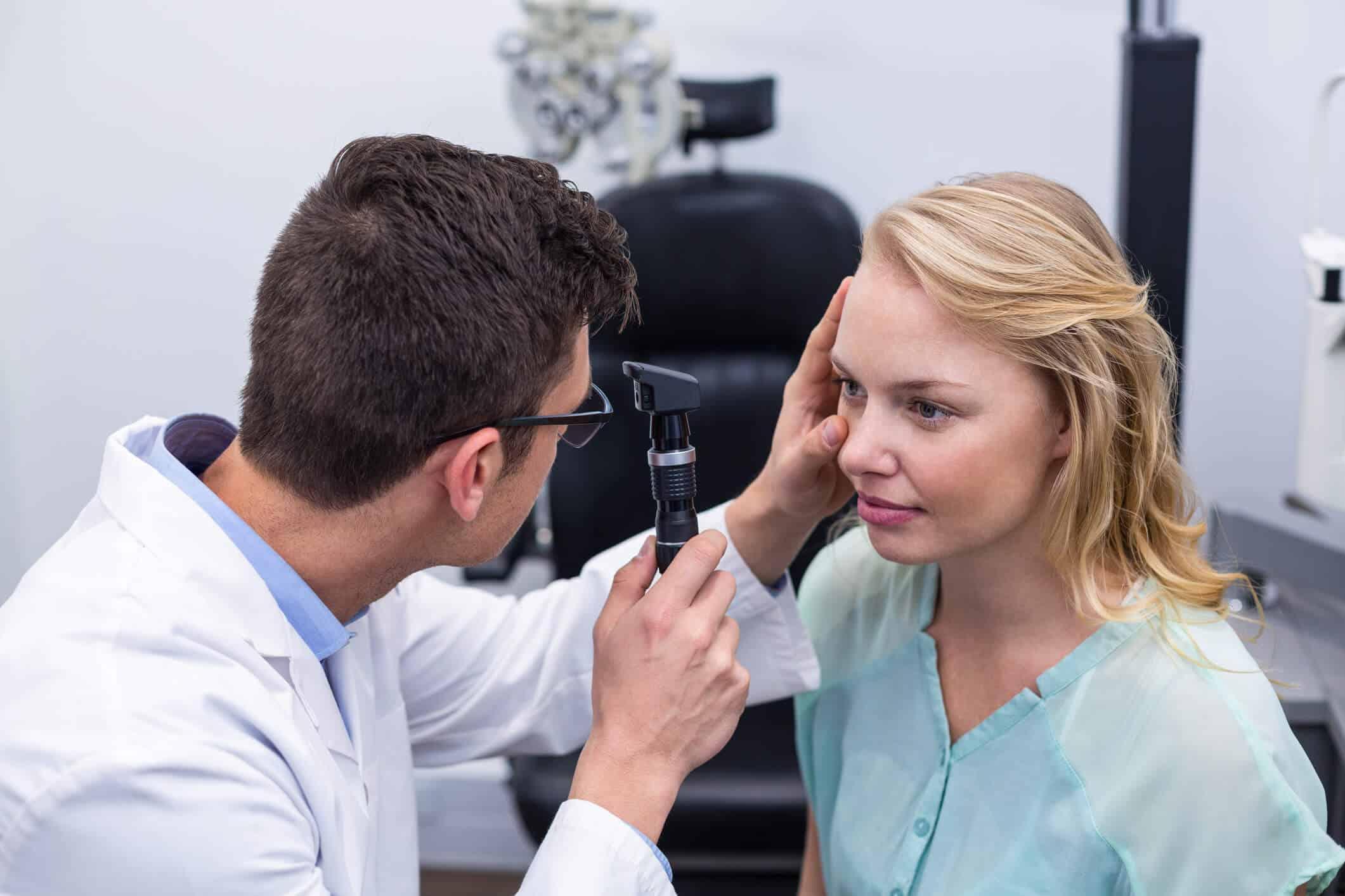 Oftalmologista homem examina paciente mulher com oftalmoscópio | para que serve o oftalmoscópio
