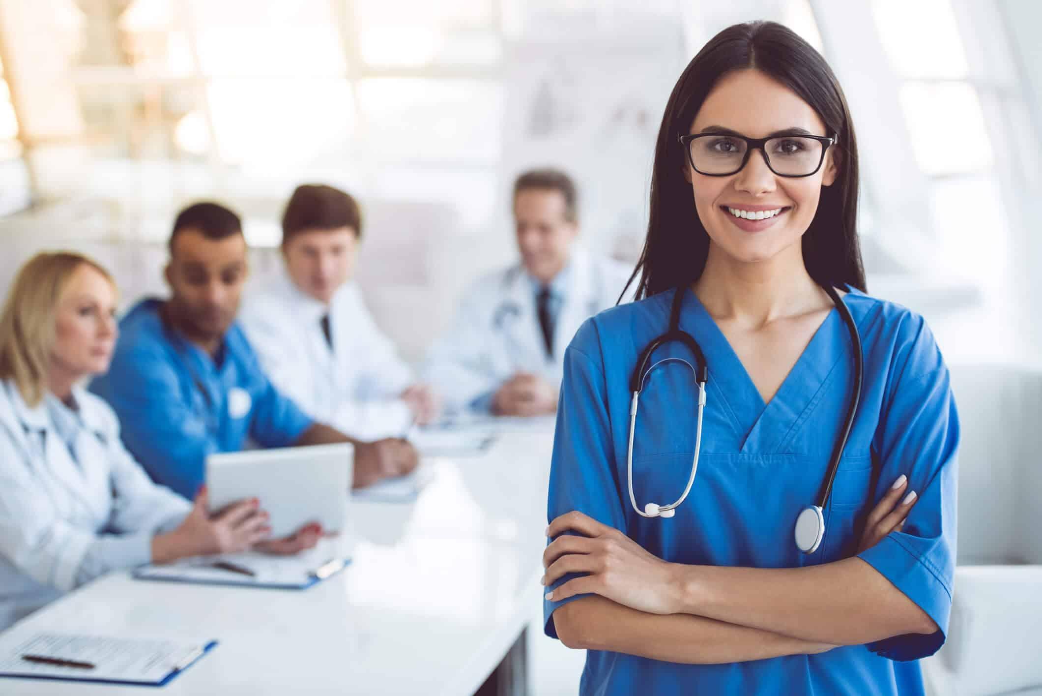 Mulher enfermeira em primeiro plano com reunião a fundo | Eventos de Enfermagem
