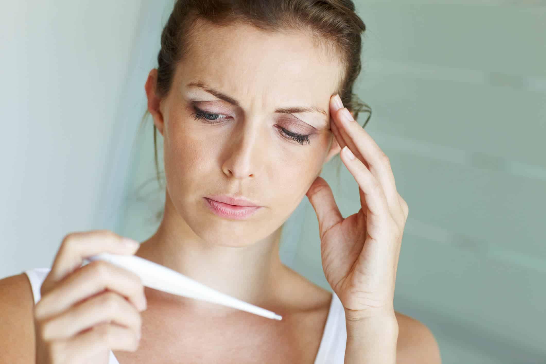 Mulher branca e jovem com a mão na cabela confere a temperatura de um termômetro digital | complicações pós-cirúrgicas