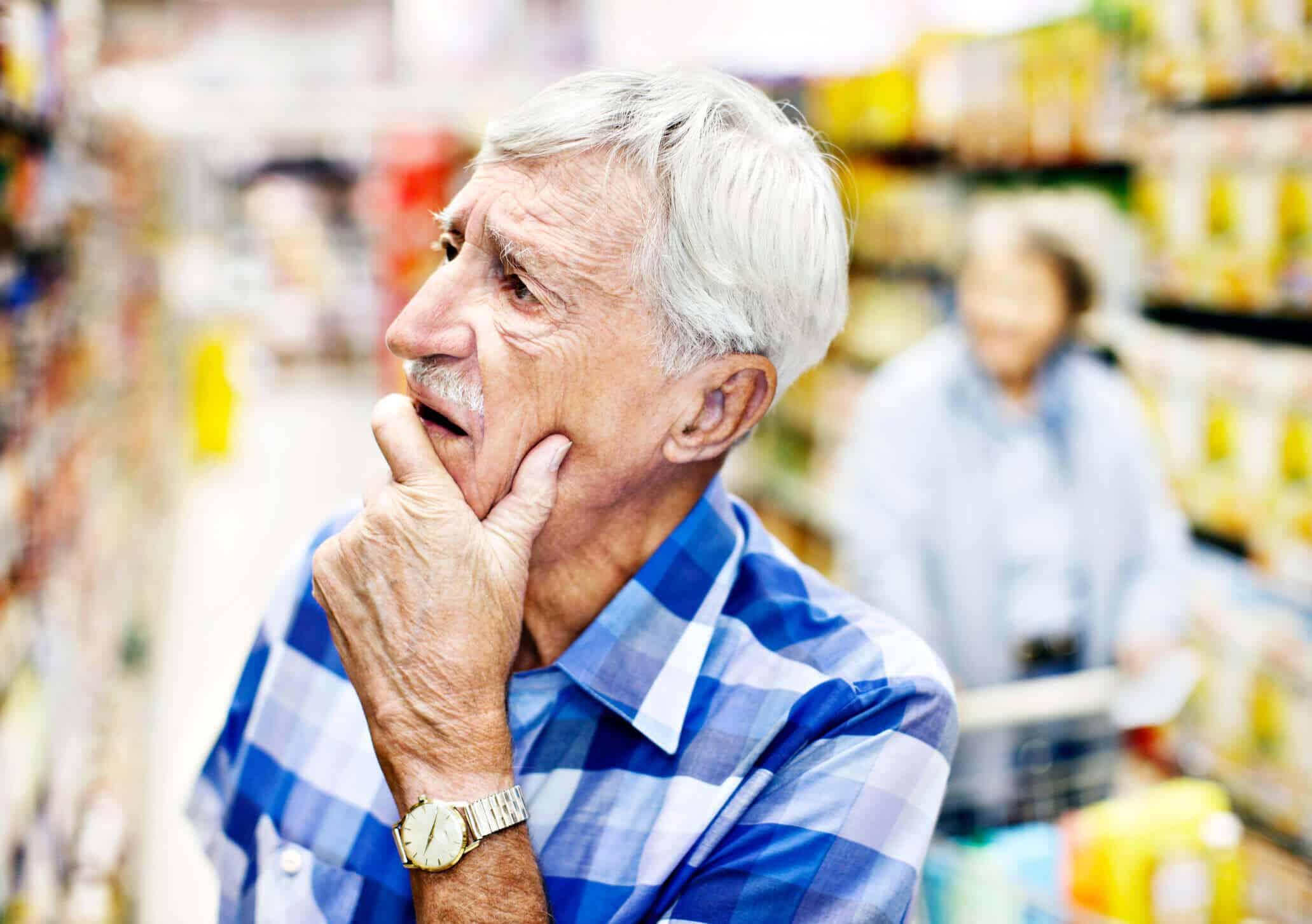 Homem branco idoso com a mão no queixo | confusão mental