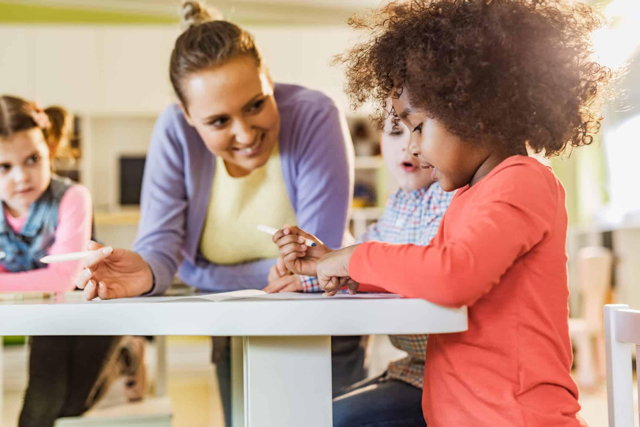 Mulher observando enquanto criança escreve | Saiba mais sobre o curso de cuidador infantil e quando fazê-lo!