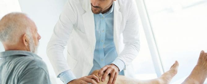 Médico jovem examina joelho joelho de idoso | Como tratar a osteoporose