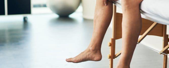 Detalhe nas pernas de uma pessoa sentada com a mão no joelho | Tipos de lesões