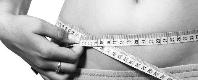 mulher medindo a cintura com uma fita métrica | melhor massageador elétrico para gordura localizada