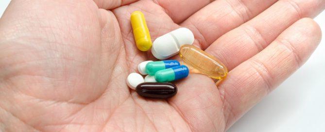 mãos masculina segurando diversos comprimidos | resistência a antibióticos