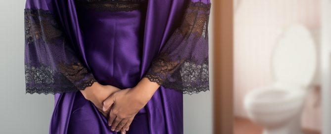 incontinencia urinaria feminina | The woman in purple satin sleepwear and robe wake up for go to restroom. People with urinary bladder problem concept